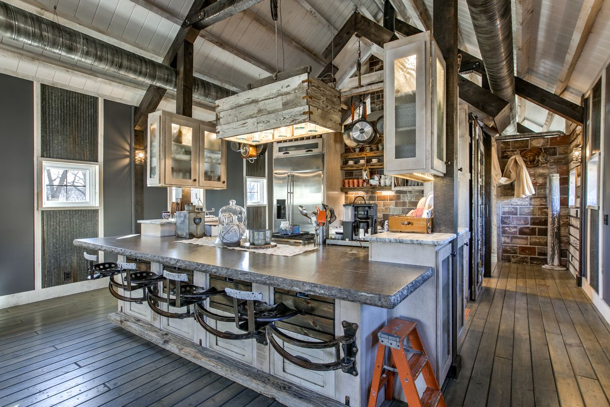 An open-concept kitchen with bar stools, shiplap, and gray counters.