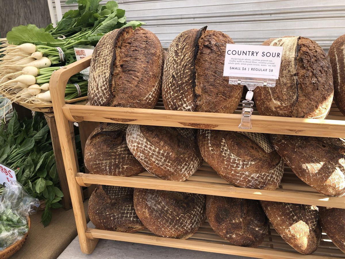 A wooden stand with loaves of fresh bread