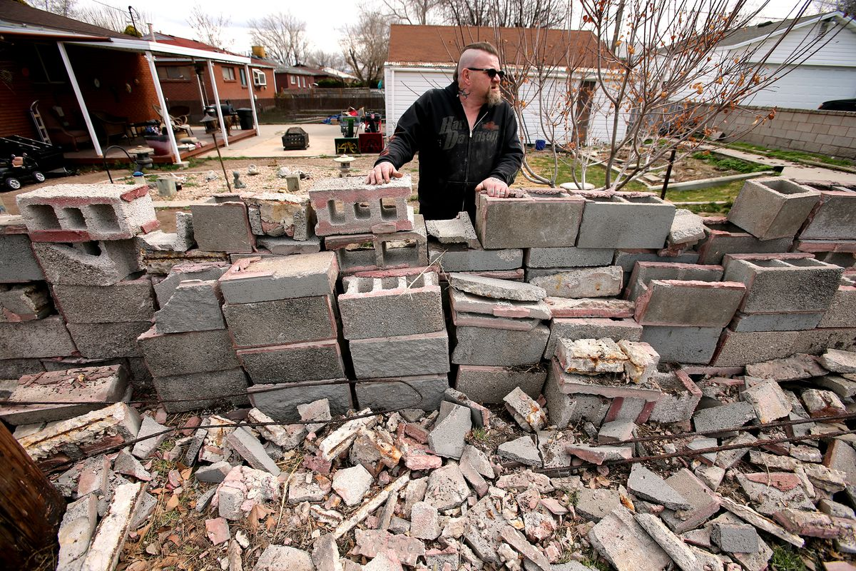Chip Simpson looks up the street from behind what was a nearly 6-foot tall block wall that was destroyed during a 5.7 magnitude quake on Wednesday, March 18, 2020.