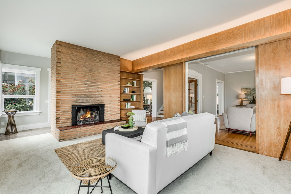 A living room has a brick fireplace, wood paneling, and a white couch.