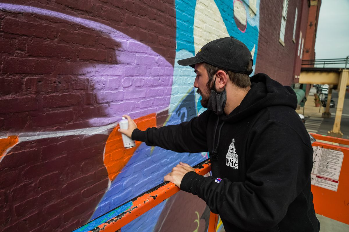 Blake Jones, one of the artists who worked on the new West Loop mural, fills in more of the outline for his towering purple rabbit.