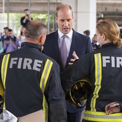 Britain's Prince William meets firefighters during a visit to the Westway Sports Centre which is providing temporary shelter for those who have been made homeless by the fire at Grenfell Tower,  in London,  Friday June 16, 2017. Relatives of those missing after a high-rise tower blaze in London are searching frantically for their loved ones, as the police commander in charge of the investigation says he hopes the death toll will not rise to three figures.