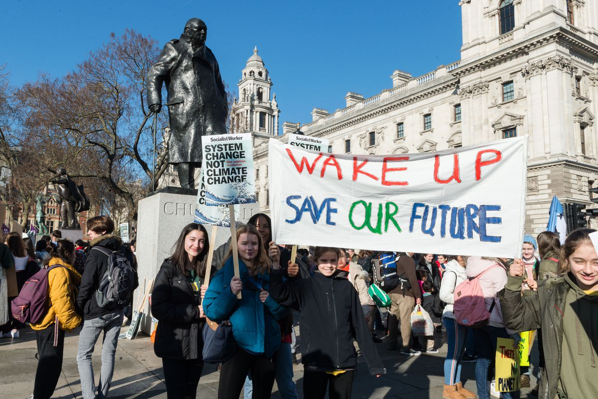 """Thousands of students went on strike in London on February 15, 2019, to protest their government's inaction on climate change. One sign reads, """"Wake up, save our future."""""""