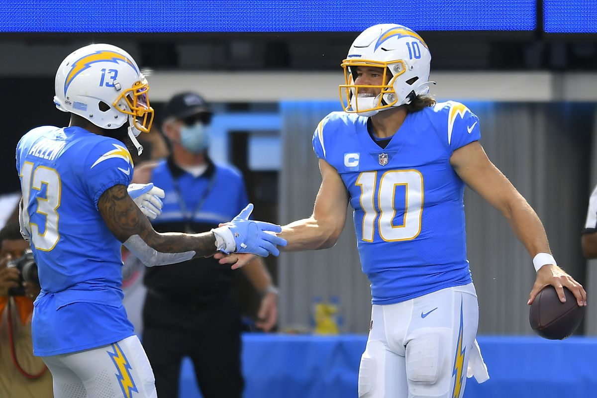 Justin Herbert #10 of the Los Angeles Chargers celebrates with Keenan Allen #13 after running for a touchdown during the second half at SoFi Stadium on October 10, 2021 in Inglewood, California.