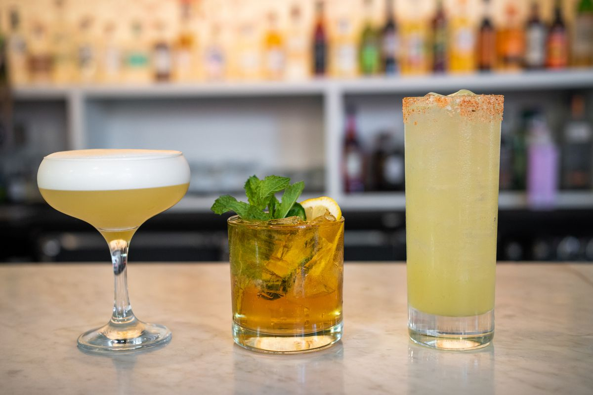 A closeup view of three cocktails, from the left: a foamy yellow drink, a brown drink garnished with mint, and a light yellow drink sprinkled with spices and salt.