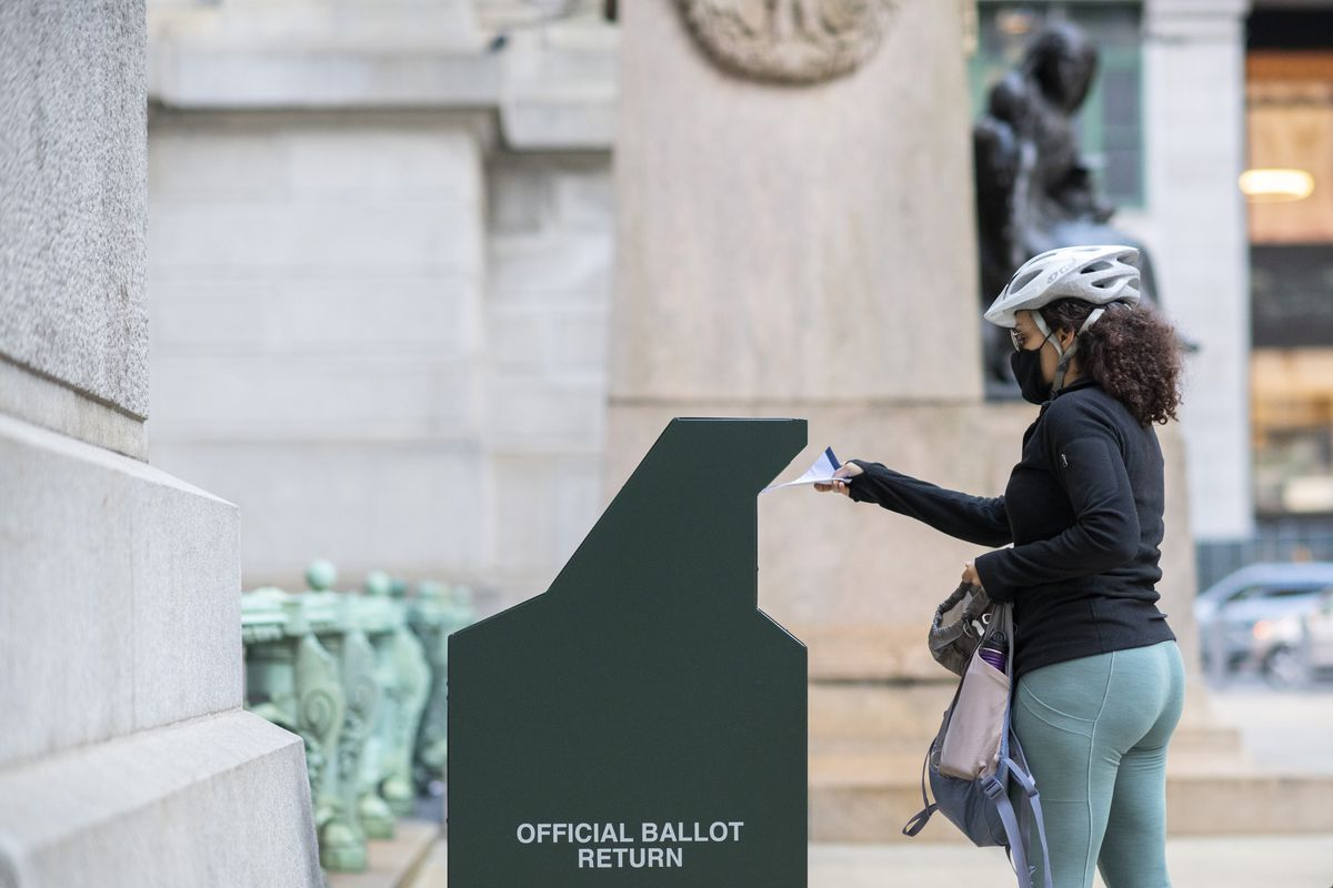 """A woman in a grey bike helmet, black mask, and glasses is seen in profile. She is placing a white envelope into a metal green receptacle that says """"Official Ballot Return"""" on the side."""