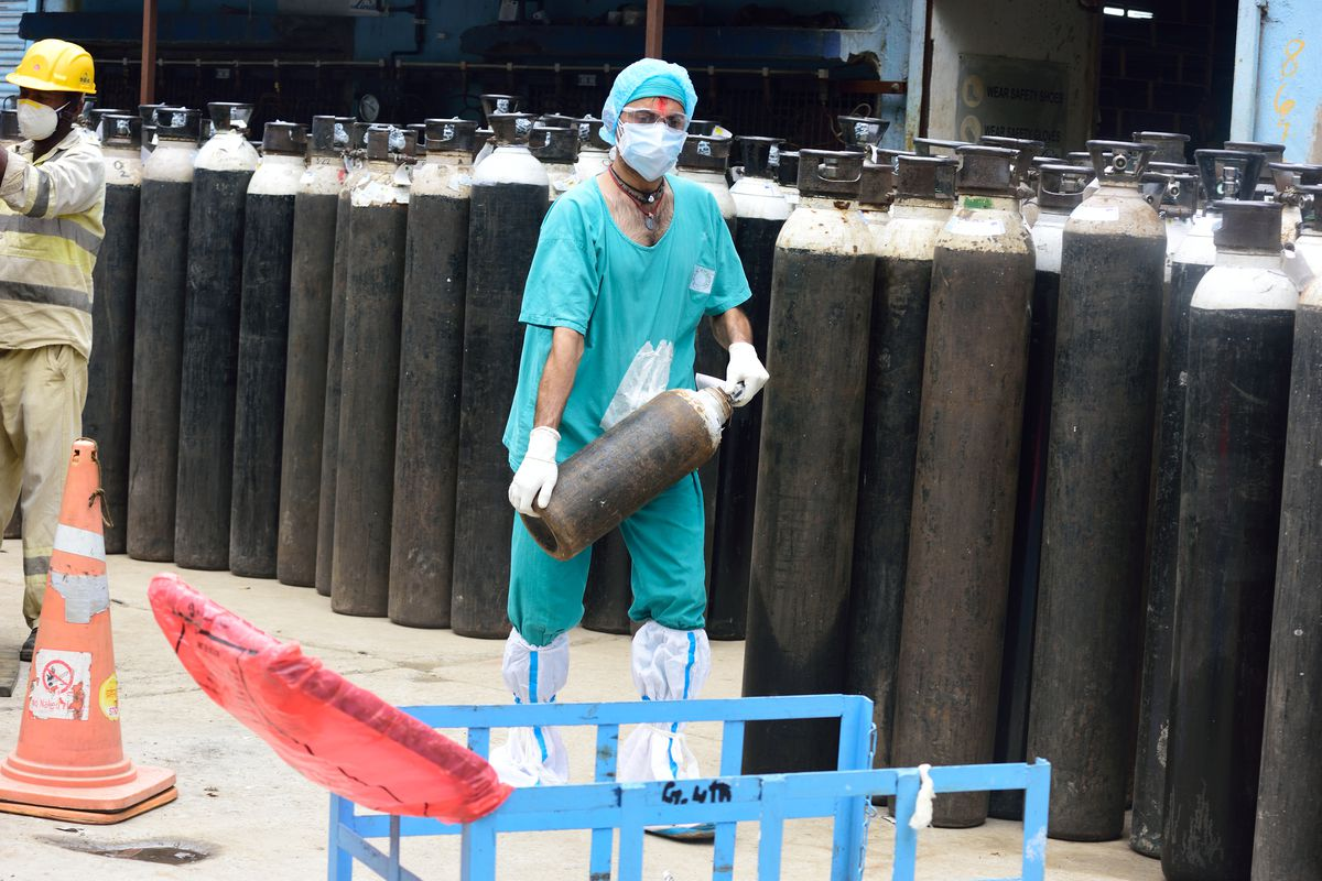 A worker wearing a face mask carries a small oxygen cylinder past a collection of large oxygen cylinders.