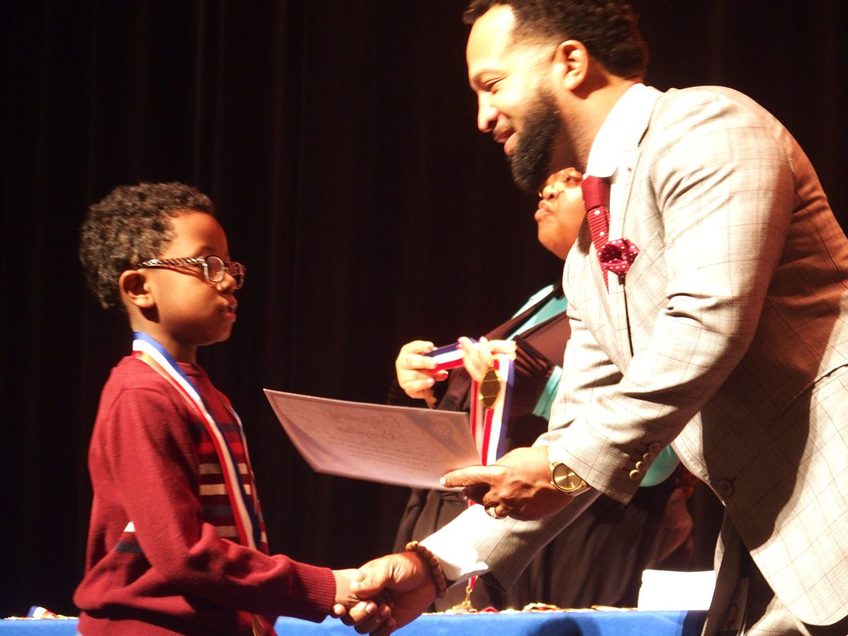Antonio Burt, the district's chief academic officer, presents a certificate to a newly identified gifted student at Shelby County Schools' induction ceremony last week.