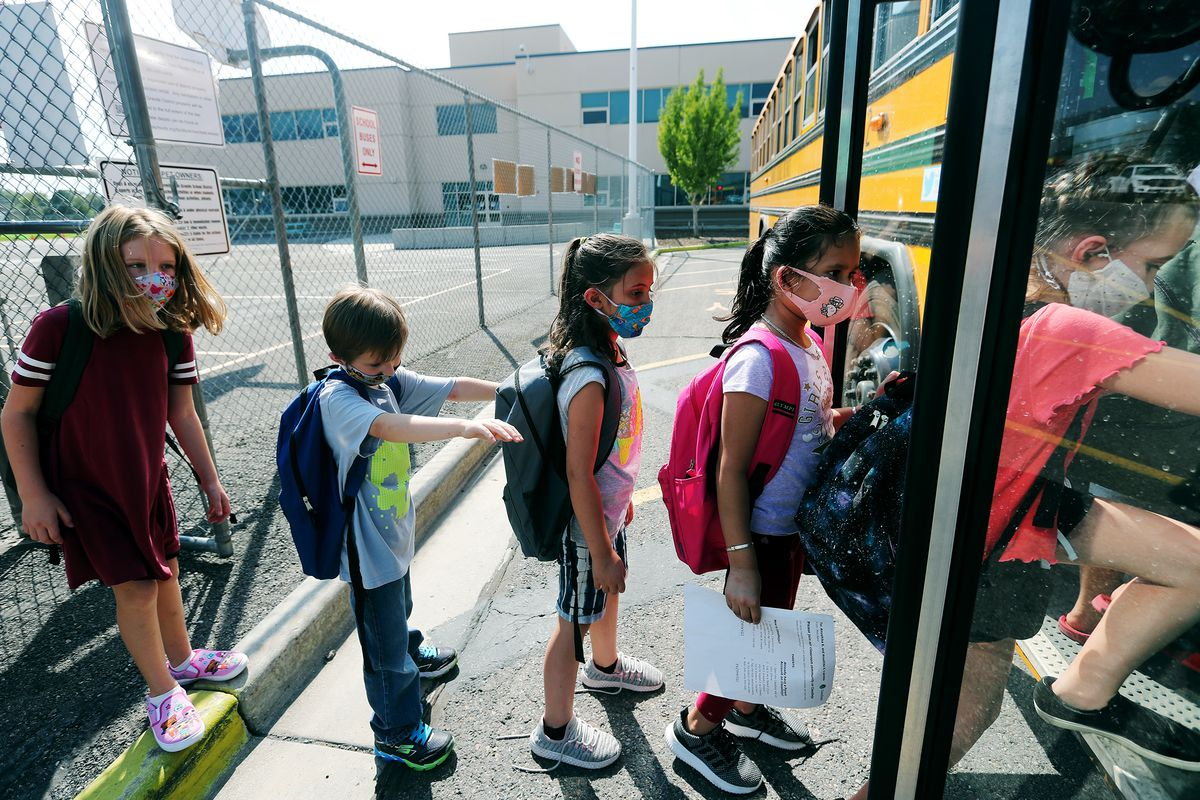 Elementary school students in South Salt Lake wear masks as the get on a bus.