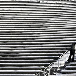 A worker removes snow from the stadium stairs before the start of an NCAA football game between the Utah Utes and Colorado Buffaloes at Rice-Eccles Stadium in Salt Lake City on Saturday, Nov. 30, 2019. The workers were removing snow from the stairs for safety, but ticket holders will have to clear off their own seats for the game.