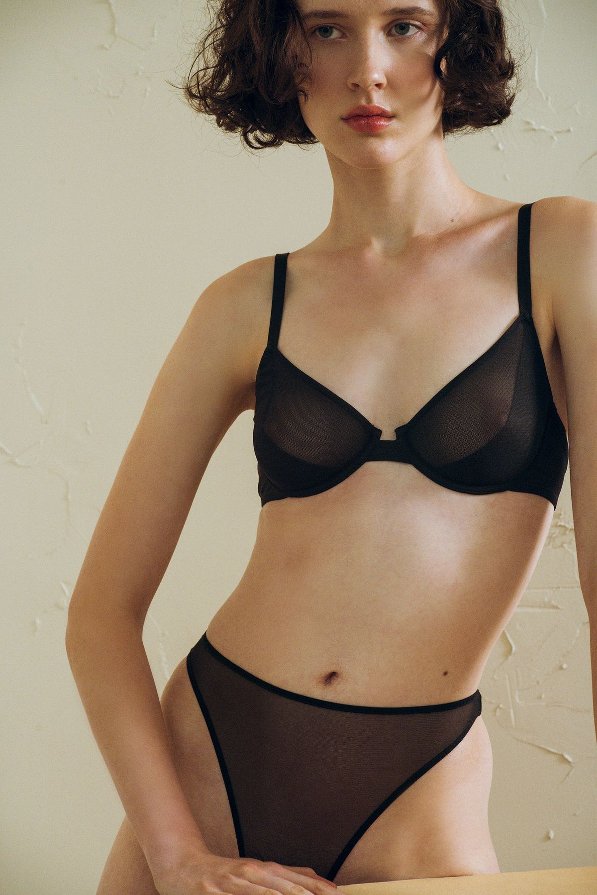 A model in a sheer black lingerie set from The Great Eros