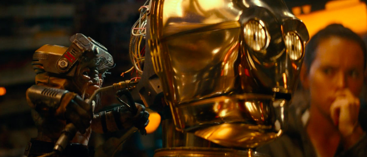 babu repairs c3po as rey watches nervously