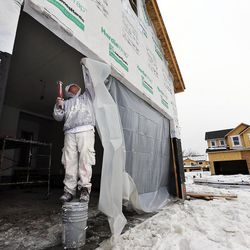 Rodrigues Zion puts up plastic sheeting in the doorway of a home being built in Farmington on Thursday, Feb. 4, 2016.