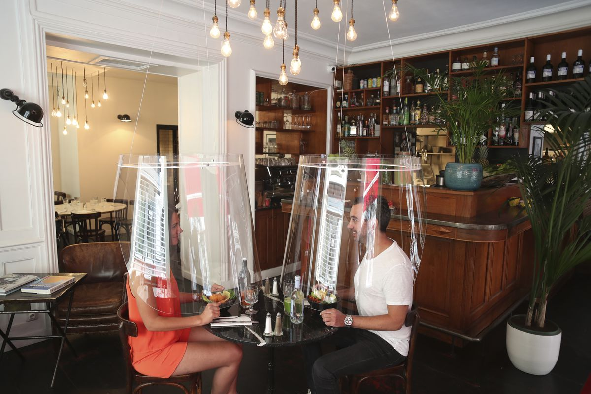 A man and a woman sit at a restaurant table, each under their own plastic shield that encases their vodies.