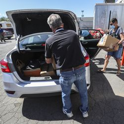 Salt Lake City Mission volunteers Rick Francom, left, Rose Eyre and Raymette Francom, right, load boxes of food into a car during the mission's Father's Day Food Box Giveaway in Salt Lake City on Friday, June 19, 2020. The mission is providing the relief to families suffering financial loss due to the COVID-19 pandemic. The volunteers loaded food boxes into cars as they drove up to the mission's Salt Lake location at 1151 South Redwood Road.