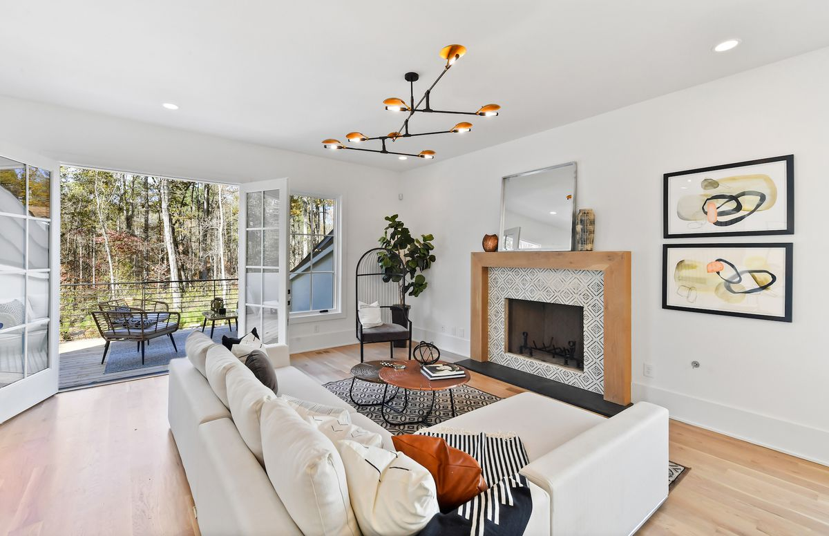 Living area with couch, coffee table, area rug, chair, houseplant, and tile fireplace.