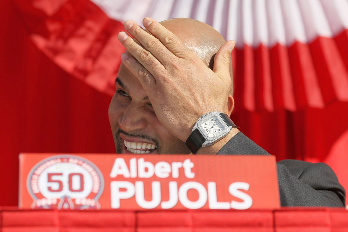 <strong>Albert Pujols</strong> sits on the stage at a public press conference.