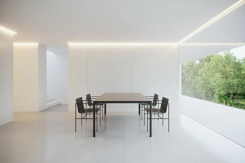 Dining room with stark white walls and black furniture.