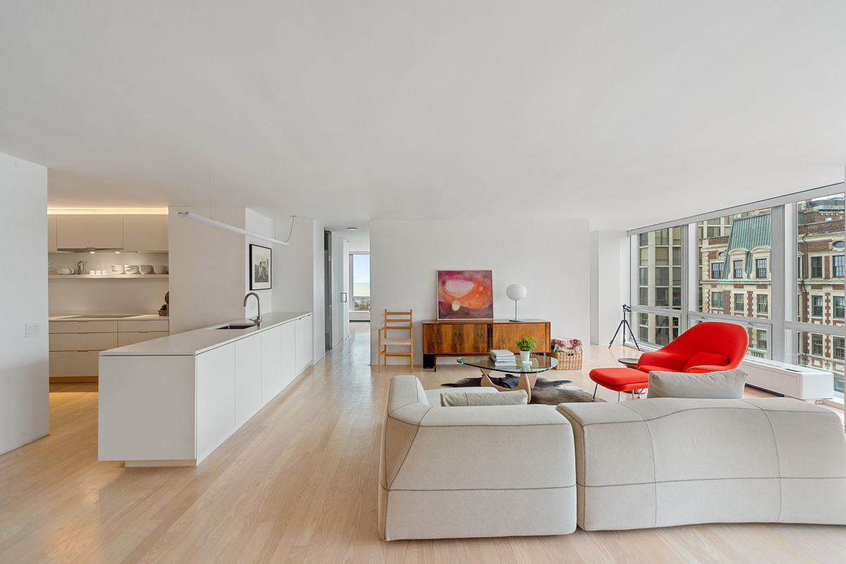 A minimalist living room with white walls and light hardwood floors. There is a minimalist kitchen counter on one side of the room and a wall of windows on the other.