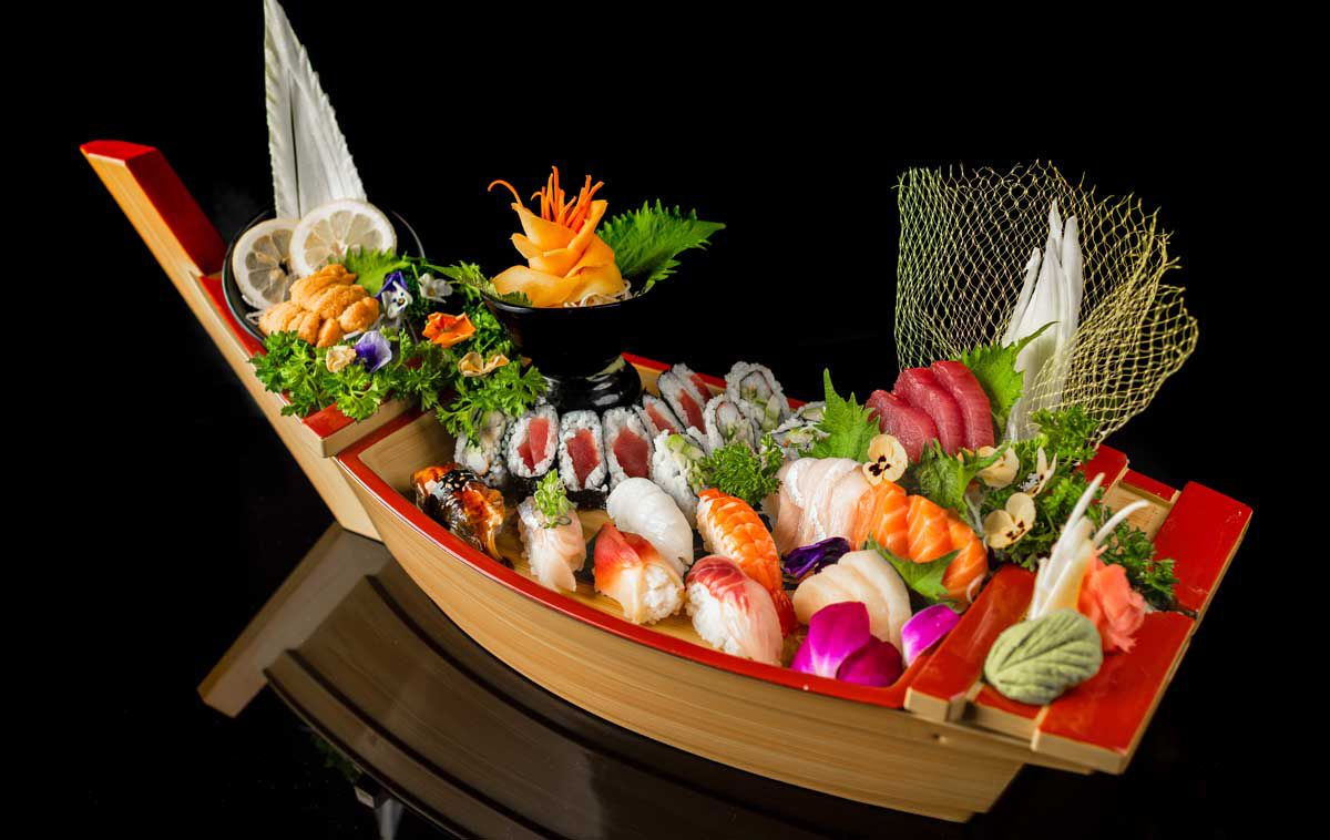 An elaborate sushi boat is isolated on a black background