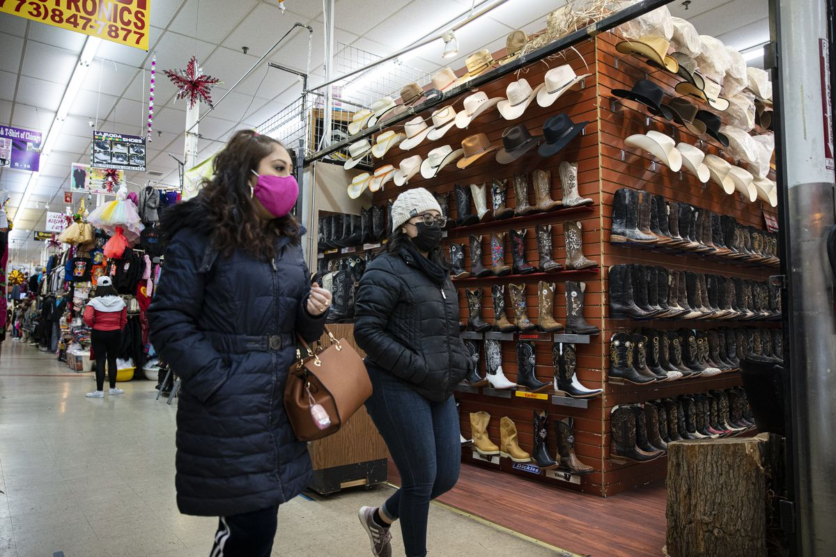 Shoppers walk past a hat and boot stall inside of the Discount Mall at 3115 W 26th St. in Little Village, Monday, Dec. 21, 2020.