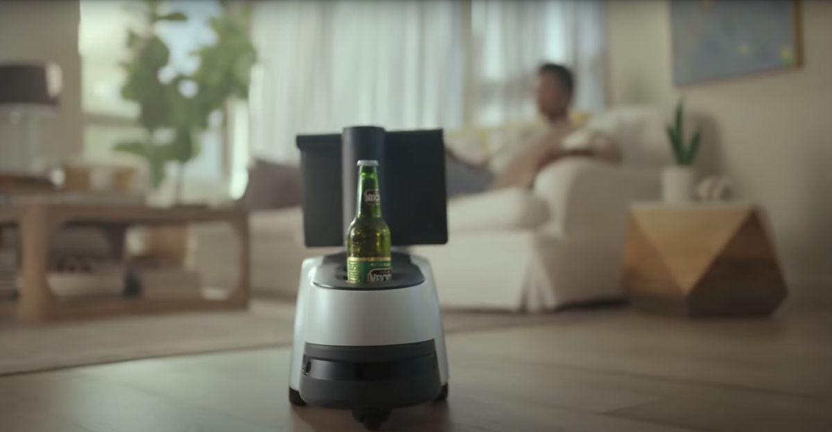 A view of the Astro robot approaching a woman. A beer rests in its cupholder.