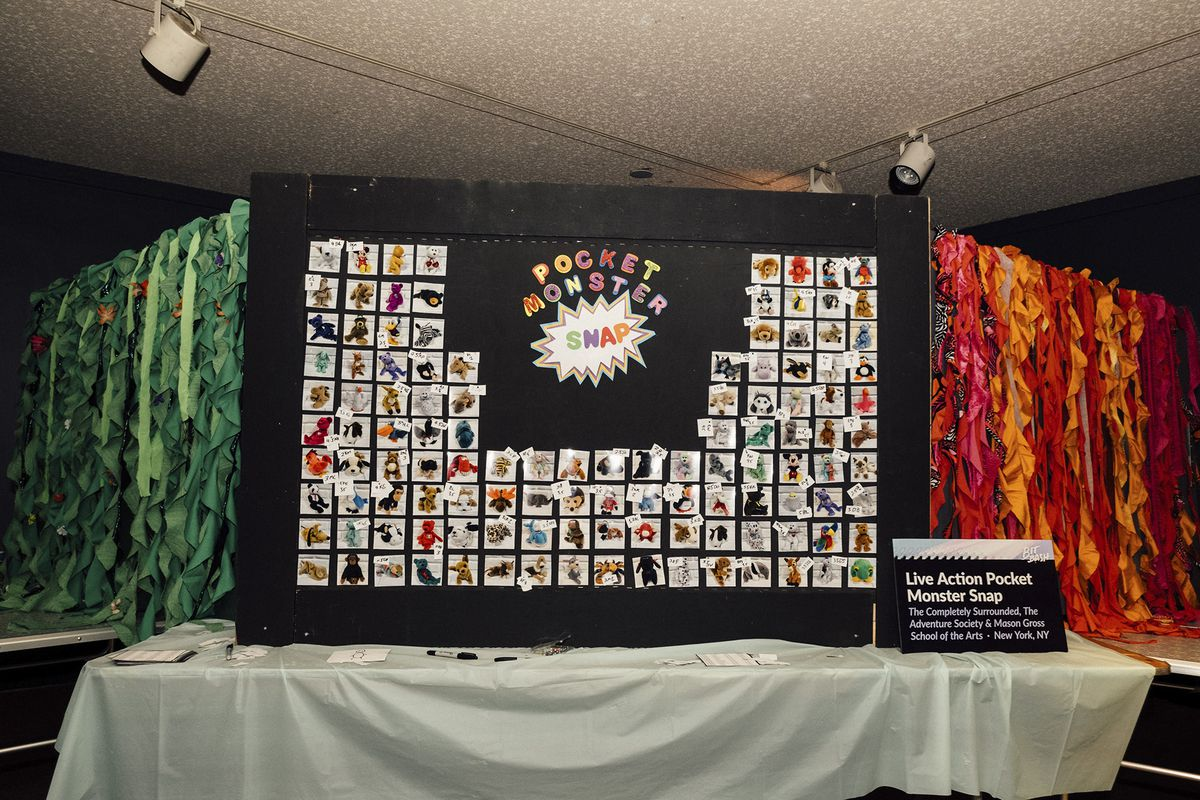 "A periodic table-like graphic shows dozens of ""Pocket Monsters"" against a large black paper background. To the left and right are backgrounds made by colored streamers, with performers holding dolls through the streamers from the other side. Bit Bash 2019"