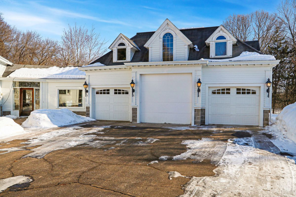 A white three-car garage has a driveway leading up to it and dormer windows.