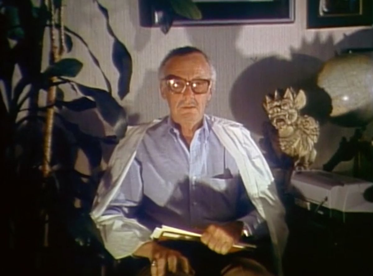 Stan Lee sitting in a chair with a book on his lap in Jugular Wine: A Vampire Odyssey (1994)