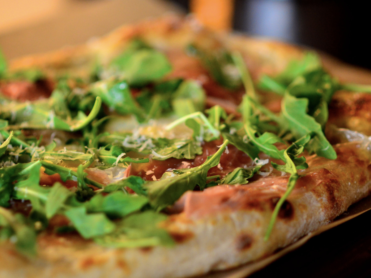 A closeup of the Morning Glory pizza at Resonate Brewery and Pizzeria, with prosciutto, mozzarella, and arugula.