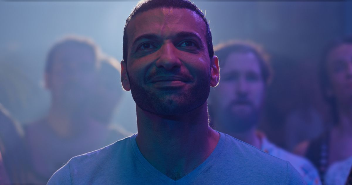 In a crowd, a Middle Eastern man smiles, covered in purple light, in Little America