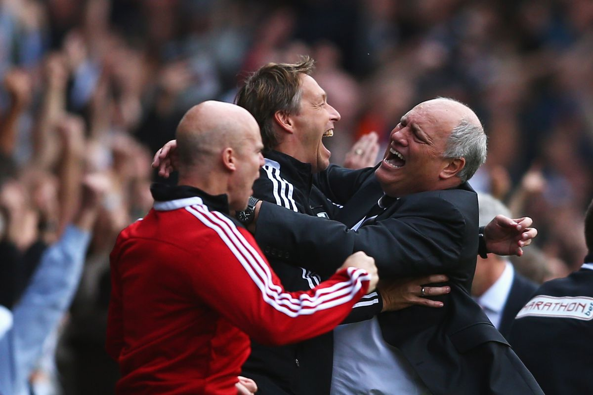 Fulham manager Martin Jol (L) celebrates the goal scored by Darren Bent of Fulham with support staff.