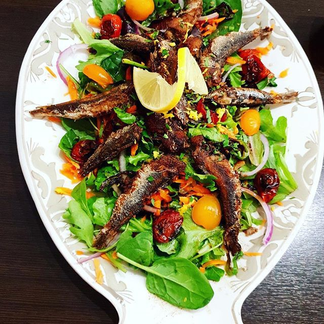 From above, a decorative serving dish filled with spinach topped with sardines arrayed around the center, cherry tomatoes, slices of red onion, and other vegetables, with a lemon wheel twisted in the center