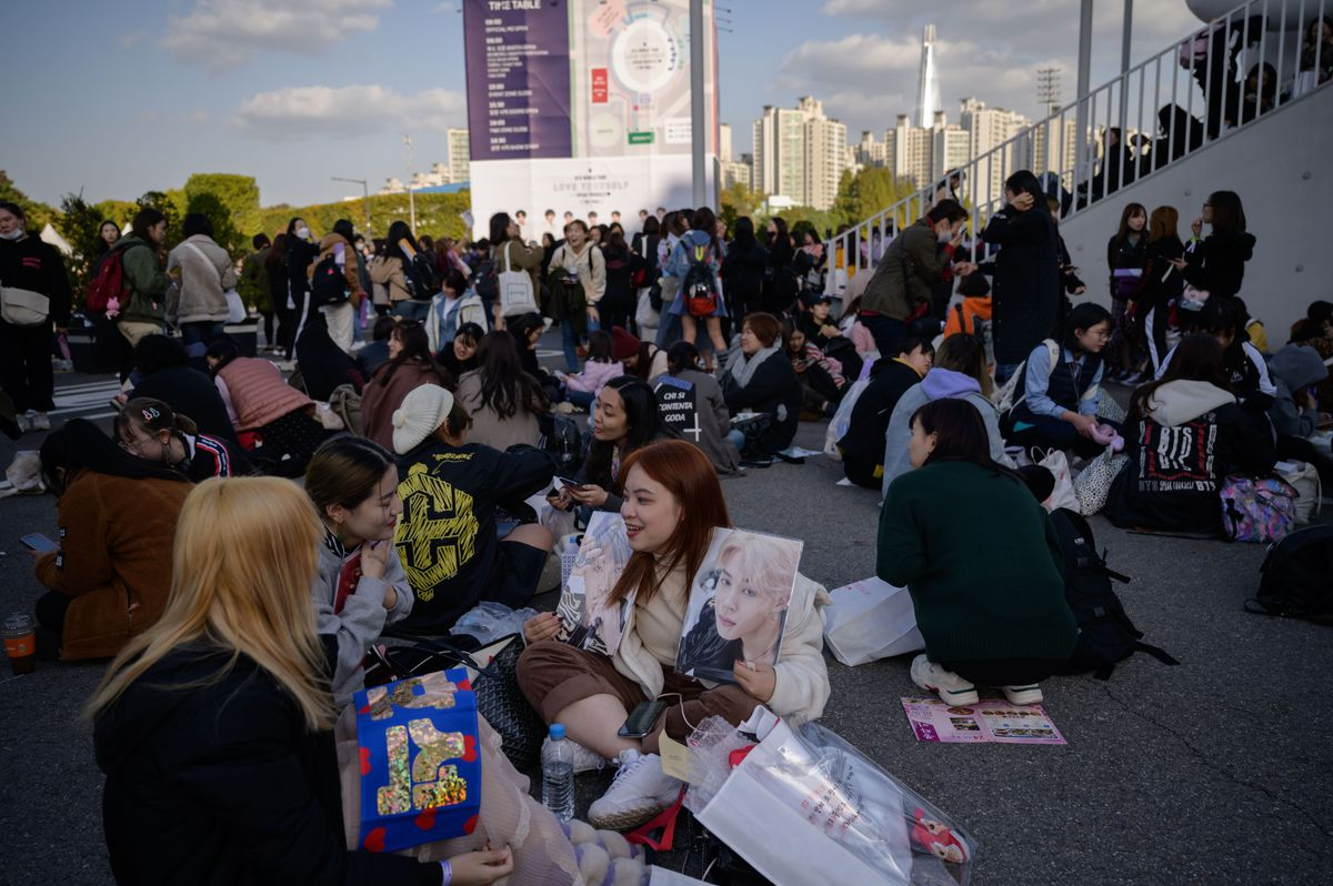 Fans sit outside the Olympic stadium in Seoul waiting for BTS's final concert of their 2019 world tour.