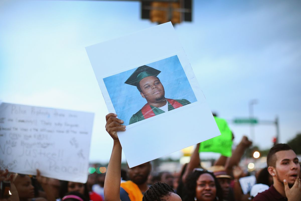 A picture of Michael Brown is held up at a protest.