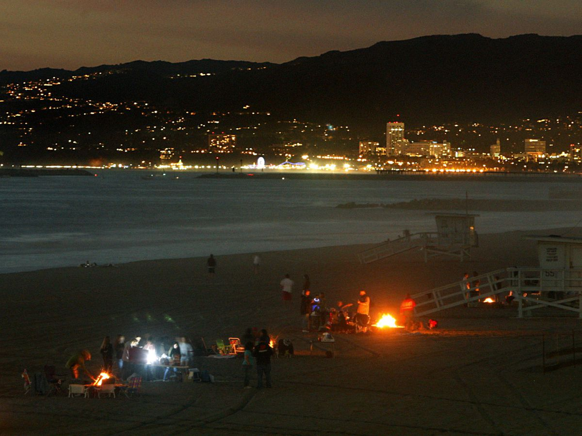 At night, fire pits glow along a stretch of beach. A peninsula illuminated in city lights is in the background.
