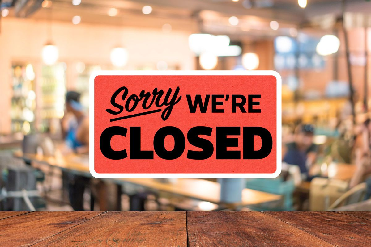 """a """"sorry, we're closed"""" sign posted above a restaurant interior"""