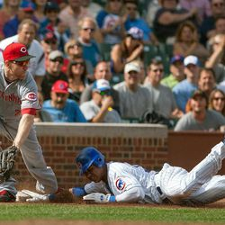 Chicago Cubs' Starlin Castro beats the ball to third with a triple in the fourth inning as Cincinnati Reds third baseman Todd Frazier reaches for the late throw in a baseball game in Chicago on Thursday, Sept. 20, 2012.