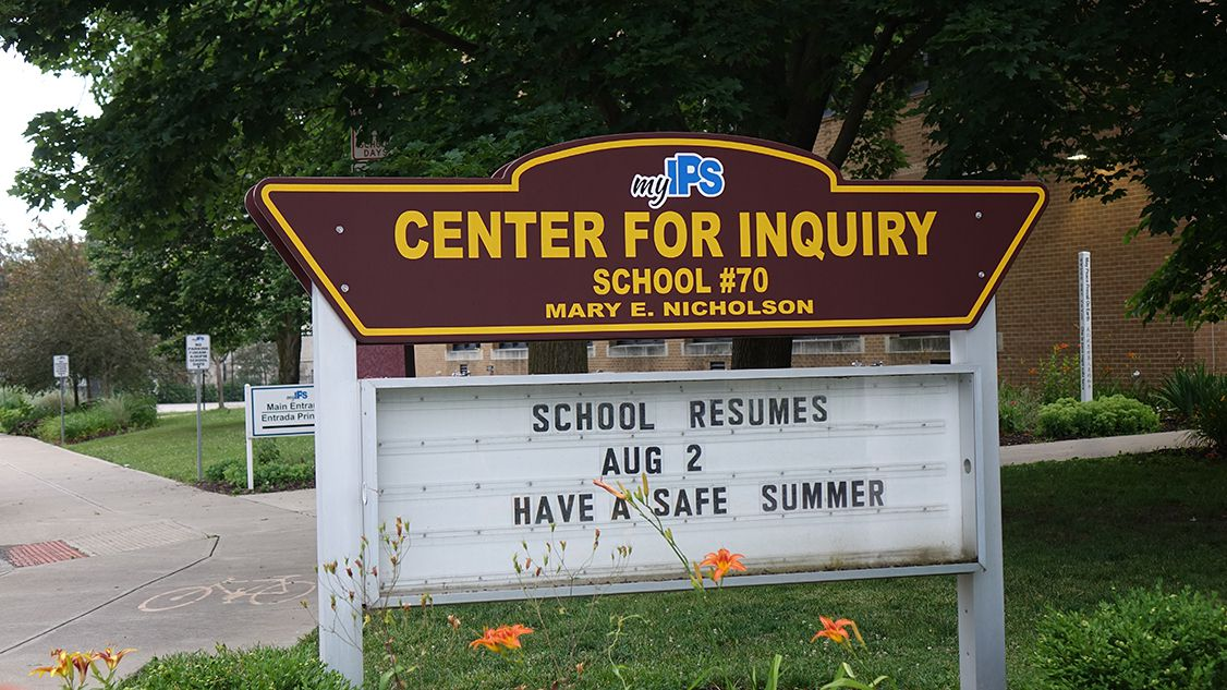 """A brown sign with yellow trim reads, """"myIPS Center for Inquiry, School #70, Mary E. Nicholson"""", with a marquee sign that reads, """"School resumes Aug 2, have a safe summer"""" in capitalized lettering."""