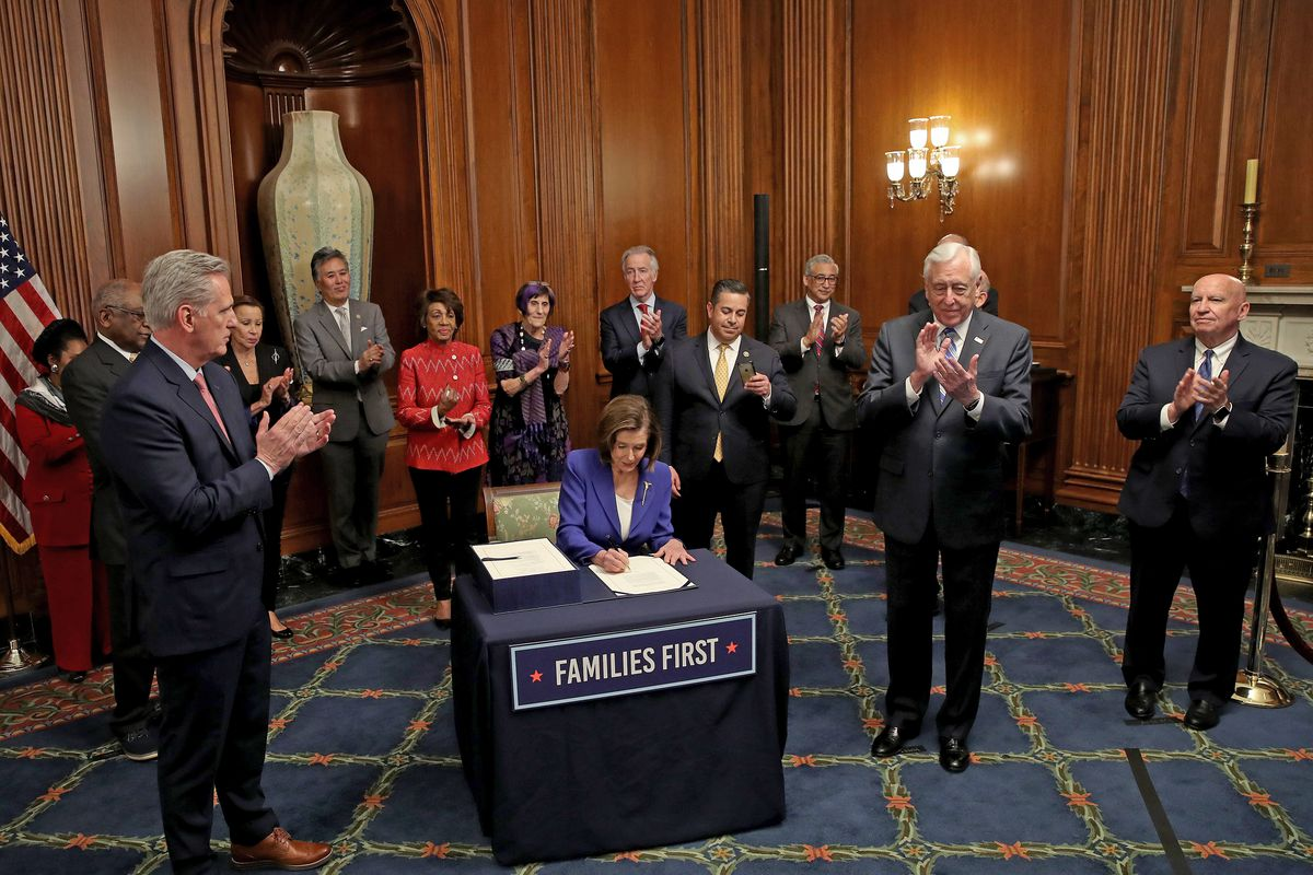 Speaker of the House Nancy Pelosi, surrounded by a bipartisan group of House members, signs the stimulus bill known as the CARES Act after the bill was passed Friday. The bill is intended to combat the economic fallout from the coronavirus pandemic.