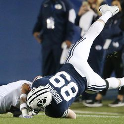 Brigham Young Cougars tight end Matt Bushman (89) is upended by a Boise State defender in Provo on Friday, Oct. 6, 2017.