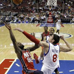 New Jersey Nets forward DeShawn Stevenson (92) shoots in front of Philadelphia 76ers center Nik Vucevic (8), from Montenegro, in the first half of an NBA basketball game on Friday, April 13, 2012, in Philadelphia. The Nets won 95-89. (AP Photo/Alex Brandon)