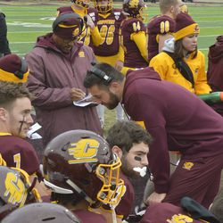 CMU assistant coaches talk with the quarterbacks on the bench.