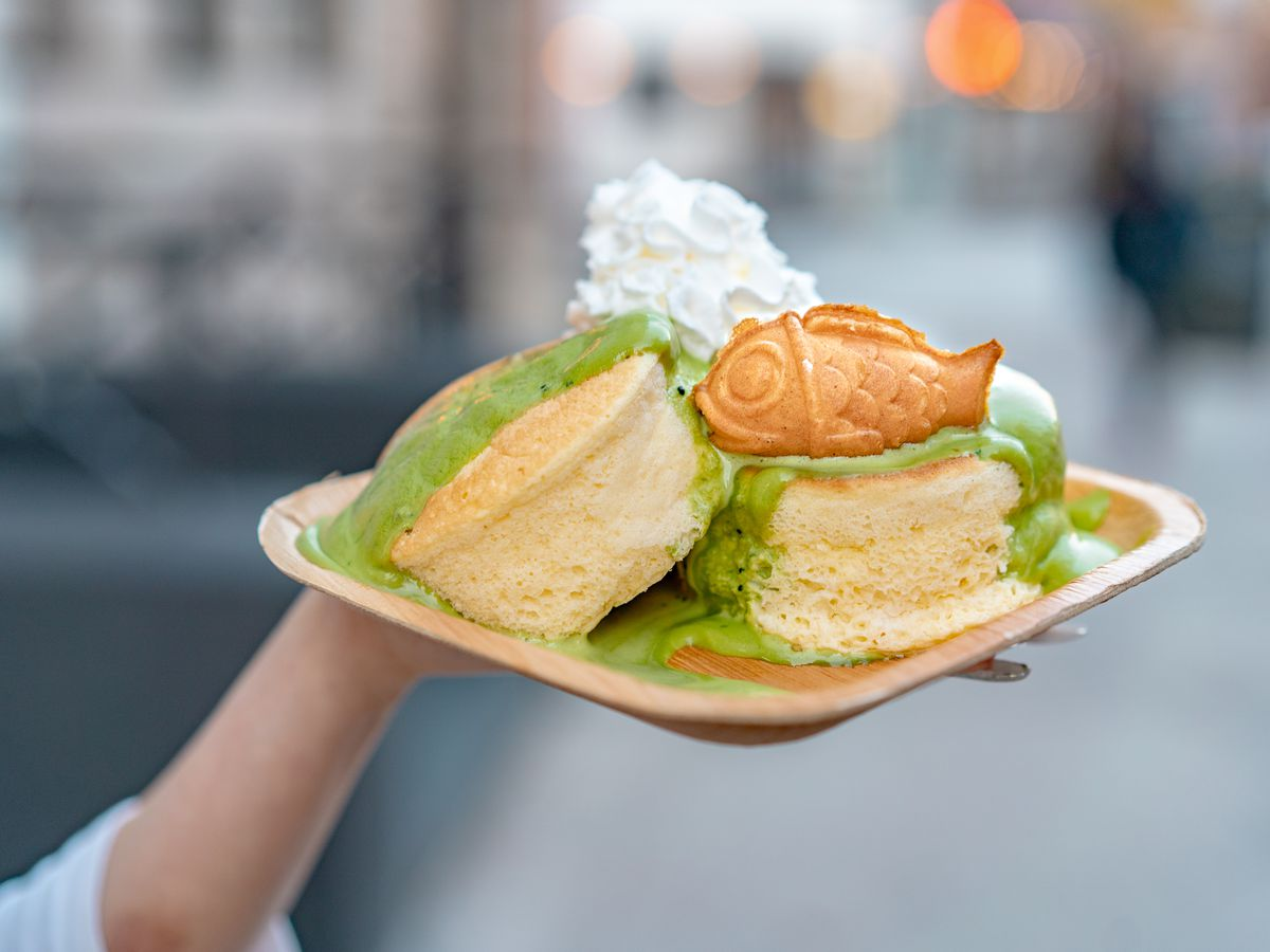 Thick, fluffy pancakes and a pressed fish-shaped dough form plated with a green matcha sauce and white whipped cream