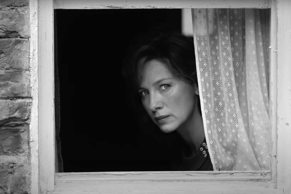 A woman peeks from behind a window in a black and white still image.