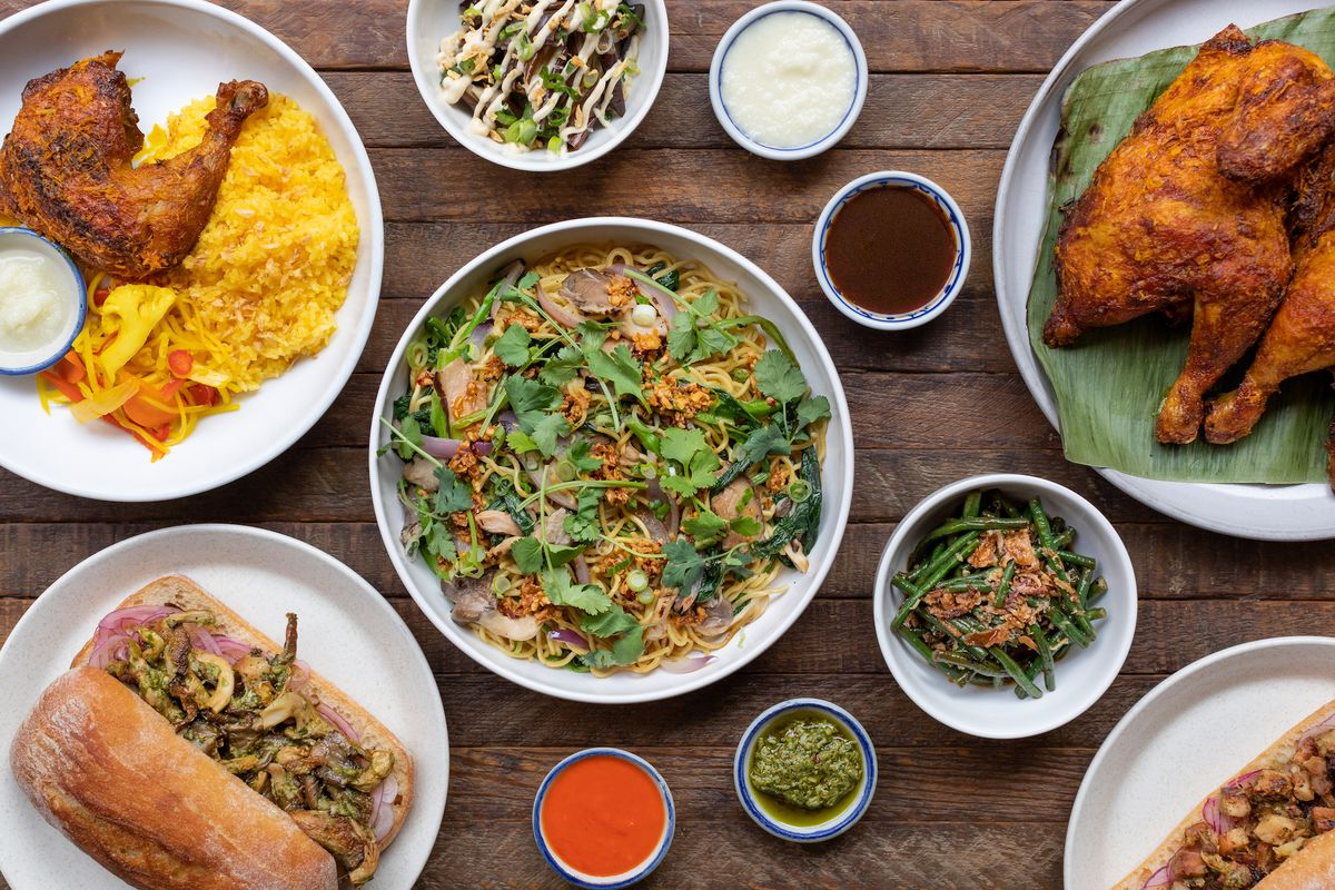 An overhead shot of bowls of Filipino food, including chicken and noodles.