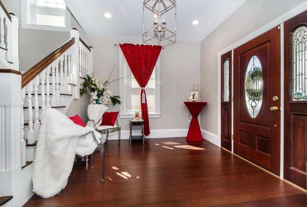 A sizable entry foyer with a stair case and a front door book-ending it, and there are two chairs.