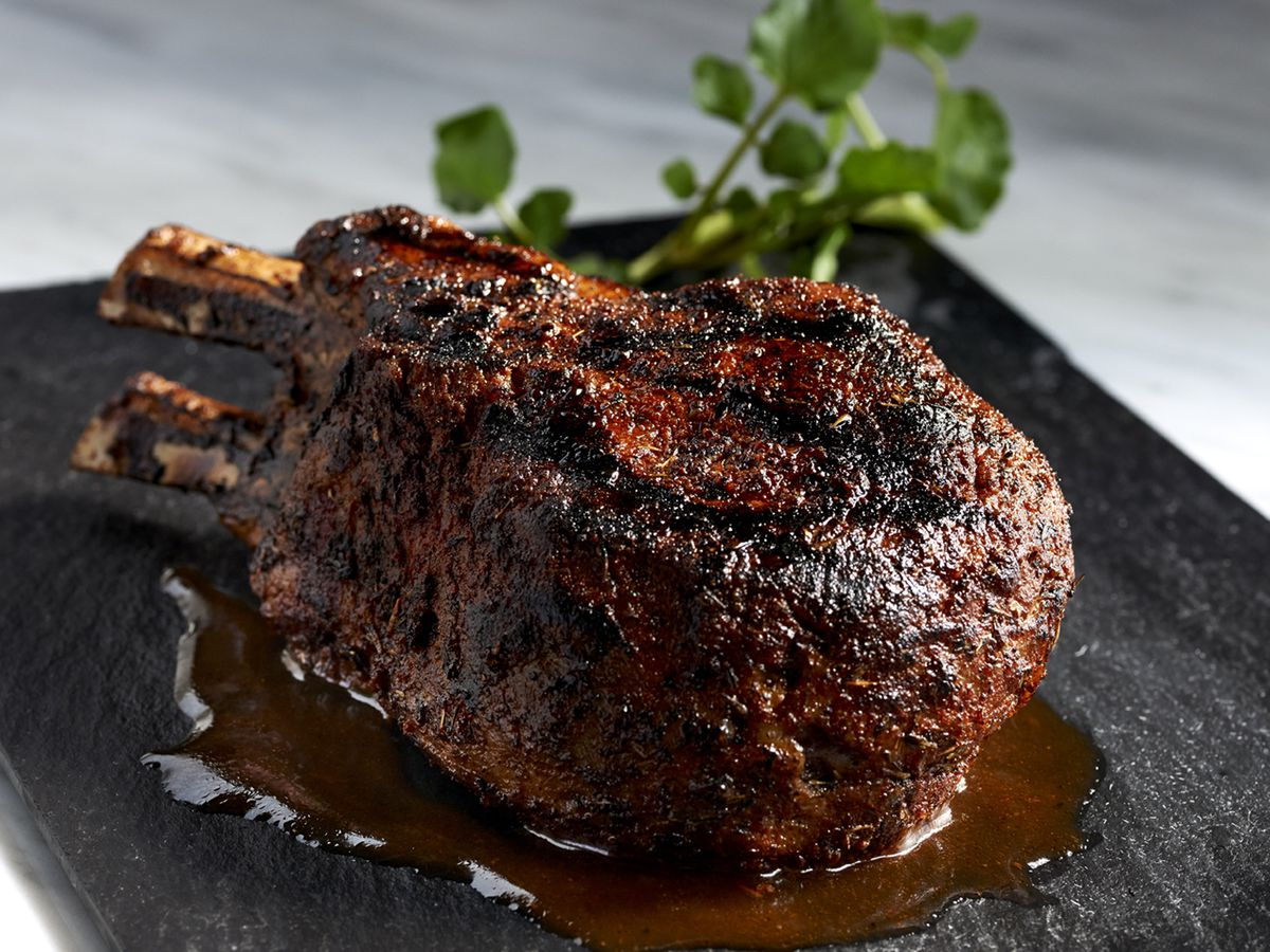 A pork chop on a black plate