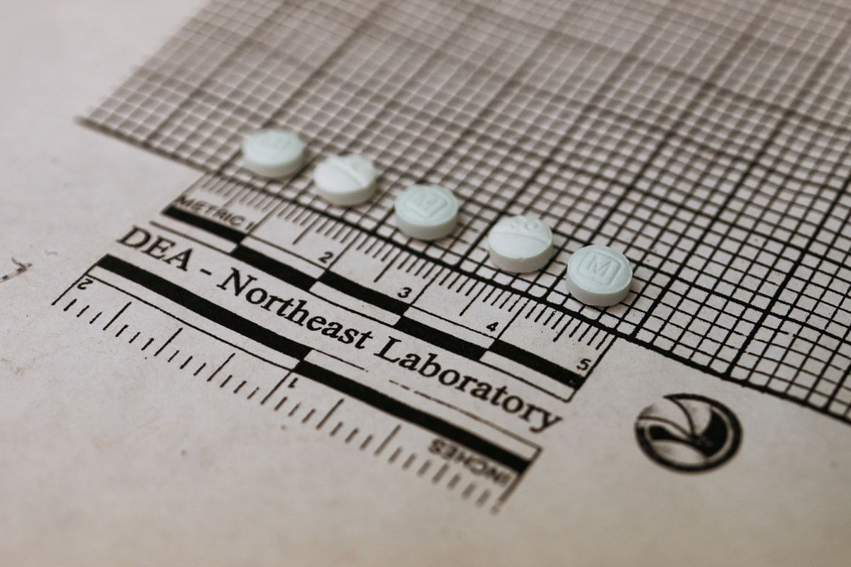 """Five small round pills lined up atop graph paper that reads, """"DEA - Northeast Laboratory."""""""