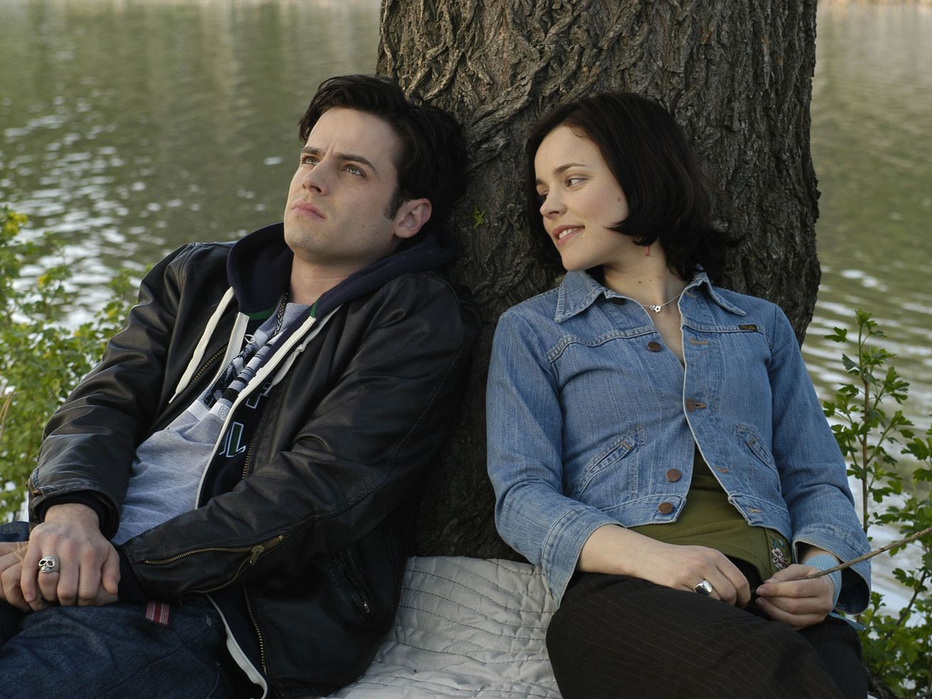 "Luke Kirby and Rachel McAdams, the stars of ""Slings & Arrows,"" sit beside a river with their backs against a tree."